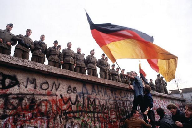 east-german-border-guards-try-to-prevent-a-crowd-climbing-onto-the-berlin-wall-in-1989-pic-getty-229561007